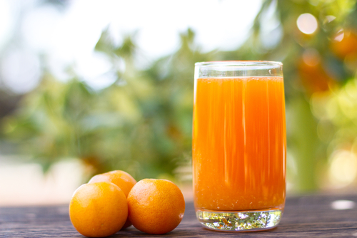 Orange juice in a glass near orange fruits